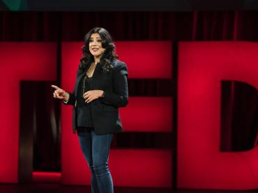 Reshma Saujani Speaking On Stage With TED Logo Behind Her