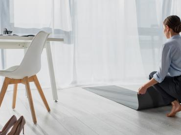 Woman In Business Outfit Kneeling Down On Yoga Matt In Office Setting