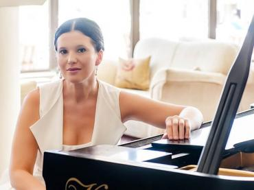 Olga Balakleets Sitting With One Arm On Piano