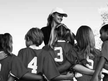 Woman Coach In Baseball Hat Surrounded By Kids In Team Uniforms