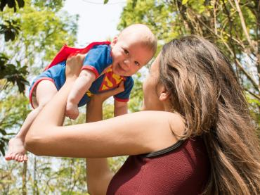 Woman Lifting  In The Air Baby Wearing A Super Man Costume