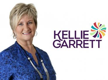 Corporate Photo Of Kellie Garrett On White Background With Her Name And Logo Beside Her