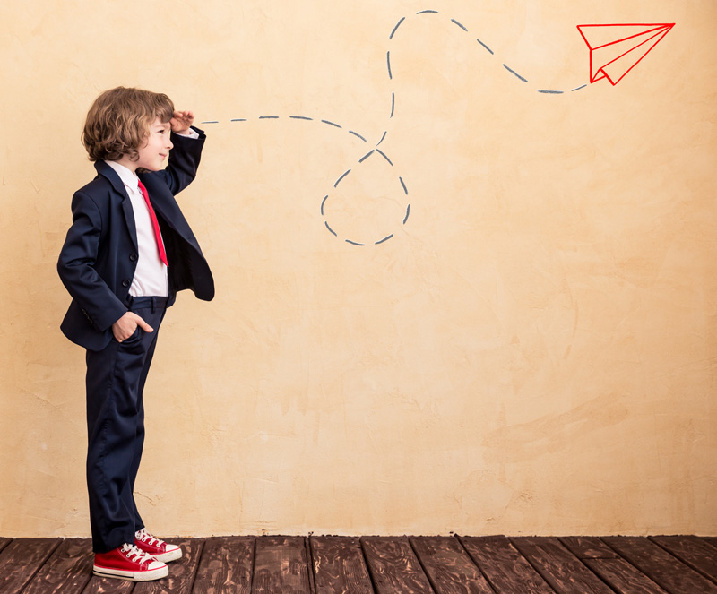 Young Boy In Business Suit With Hand Over Eyes Looking Into Distance With Drawing of Paper Plane On Wall