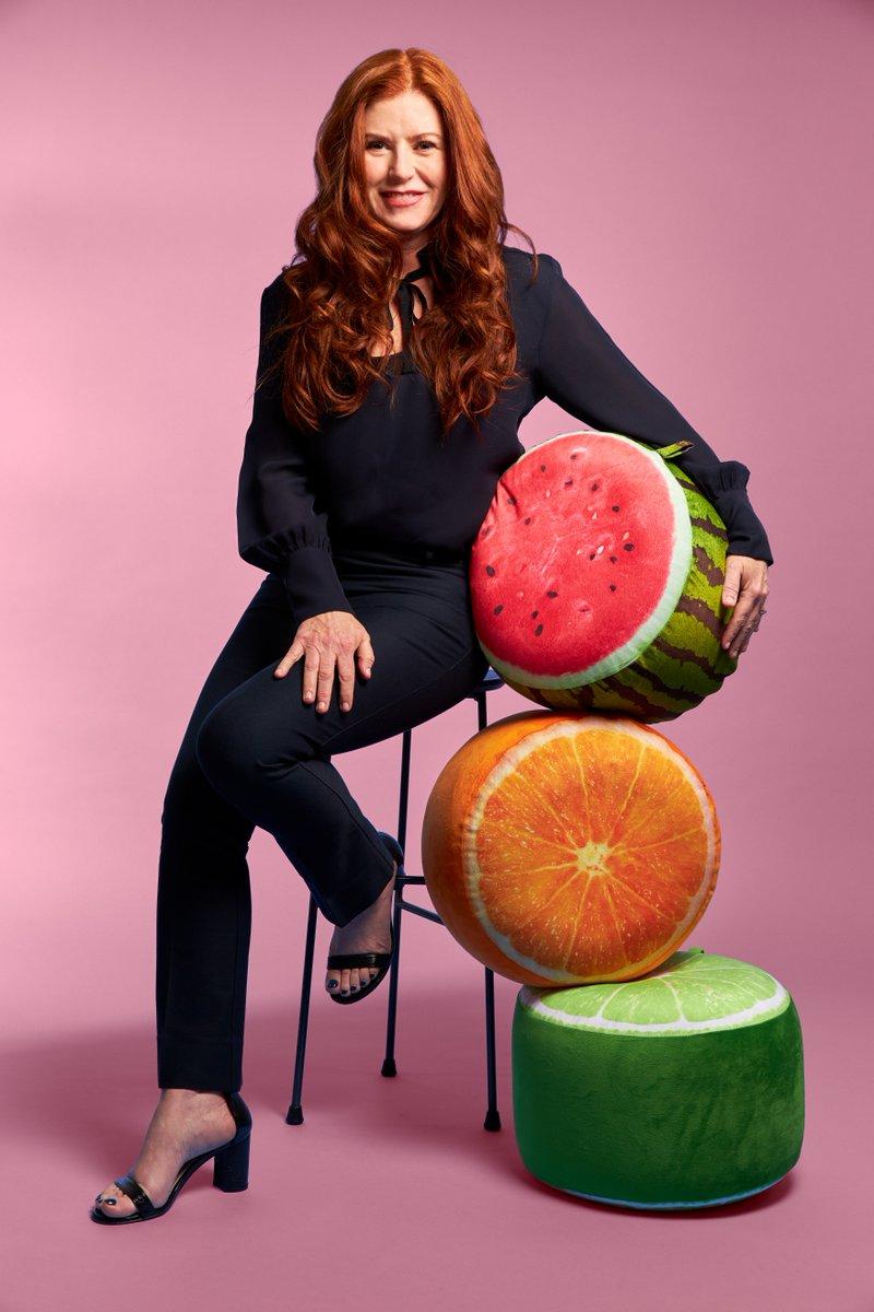 Kara Goldin Sitting On Stool With Pink Background Holding Plush Fruits