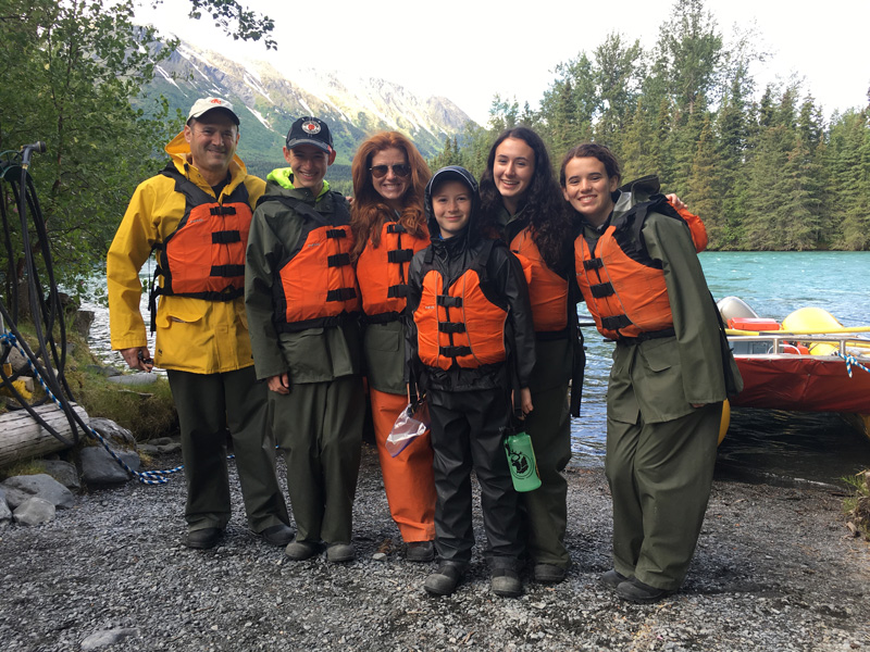 Kara Goldin And Family With Life Vests Standing By River Side