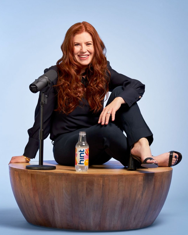 Kara Goldin Smiling And Sitting By Microphone And Bottle Of Hint Water