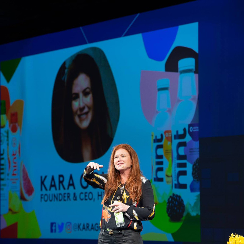 Kara Goldin On Stage Delivering Speech With Hint Water Bottle In Her Hand And Large Screen In Background