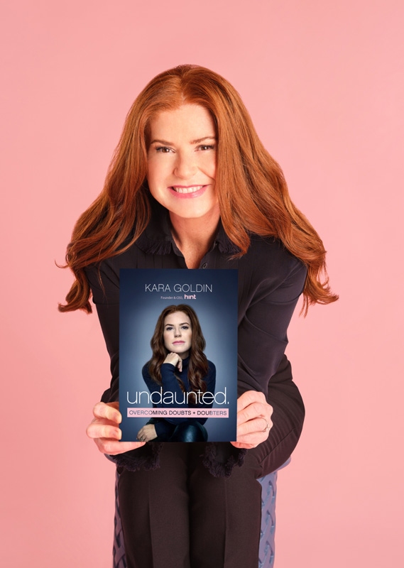 Kara Goldin Holding Her Book Undaunted On A Pink Background