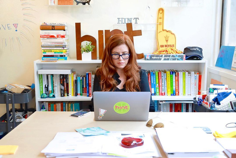 Kara Goldin Working At Desk On Laptop In Hint Water Office