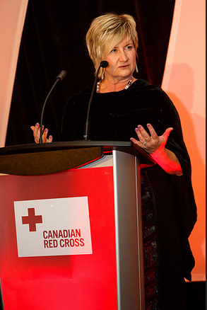 Kelly Garrett Speaking At Podium With Canadian Red Cross Sign