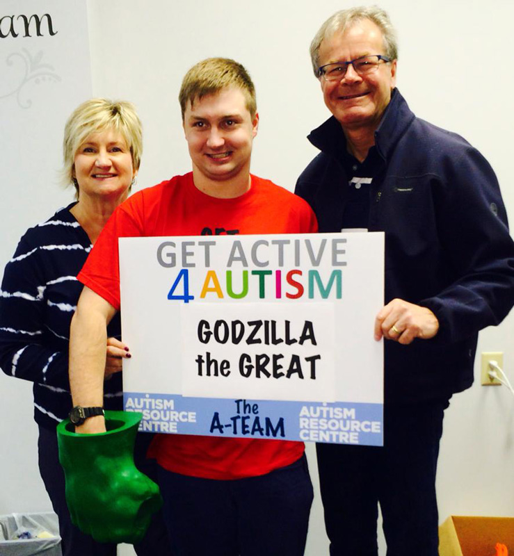 Kelly Garrett And Her Husband Supporting Their Son ConnorHolding Sign Godzilla the Great InRaising Money Autism Resource Centre