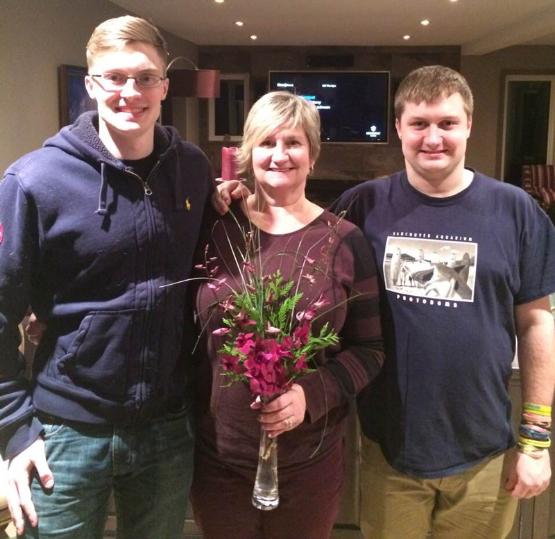 Kellie Garrett Holding Flower In Vase With Her Sons Max And Connor