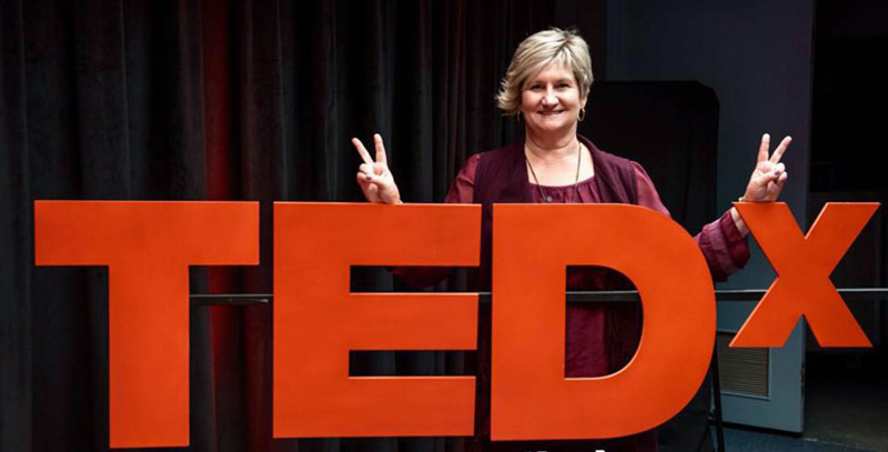 Kelly Garrett Posing In Front Of TEDx Sign Giving Peace Sign With Fingers