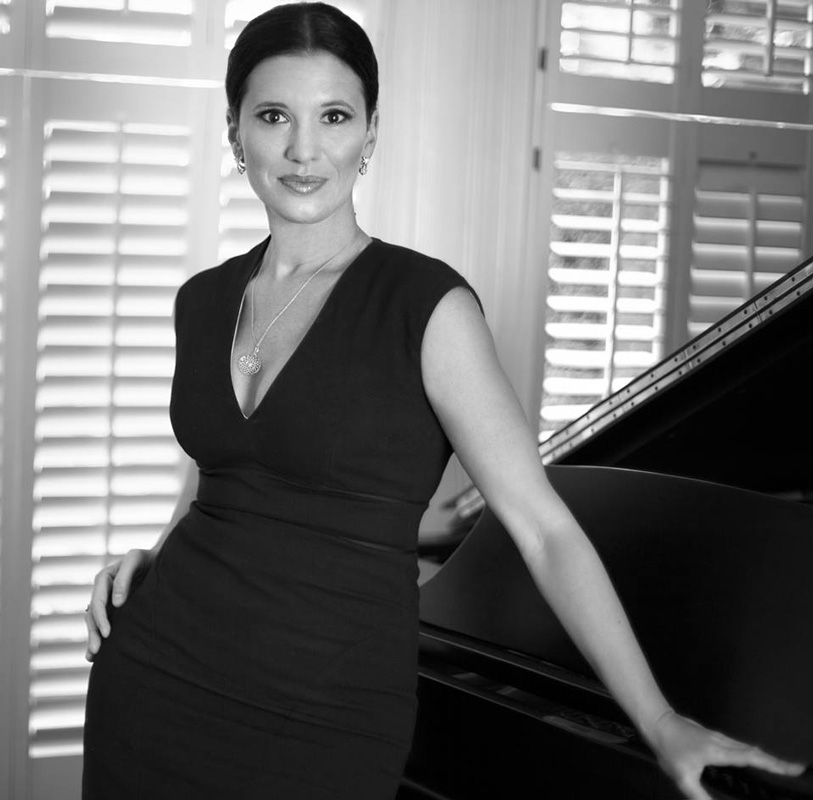 Black And White Photo Of Olga Balakleets In Black Dress Leaning On Piano
