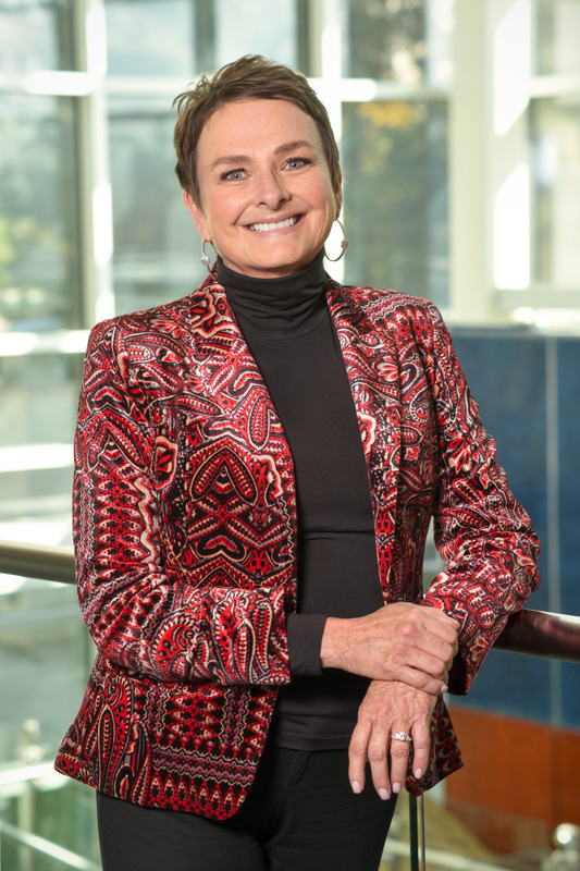 Smiling Pam Klein In Red Pattern Jacket Corporate Photo