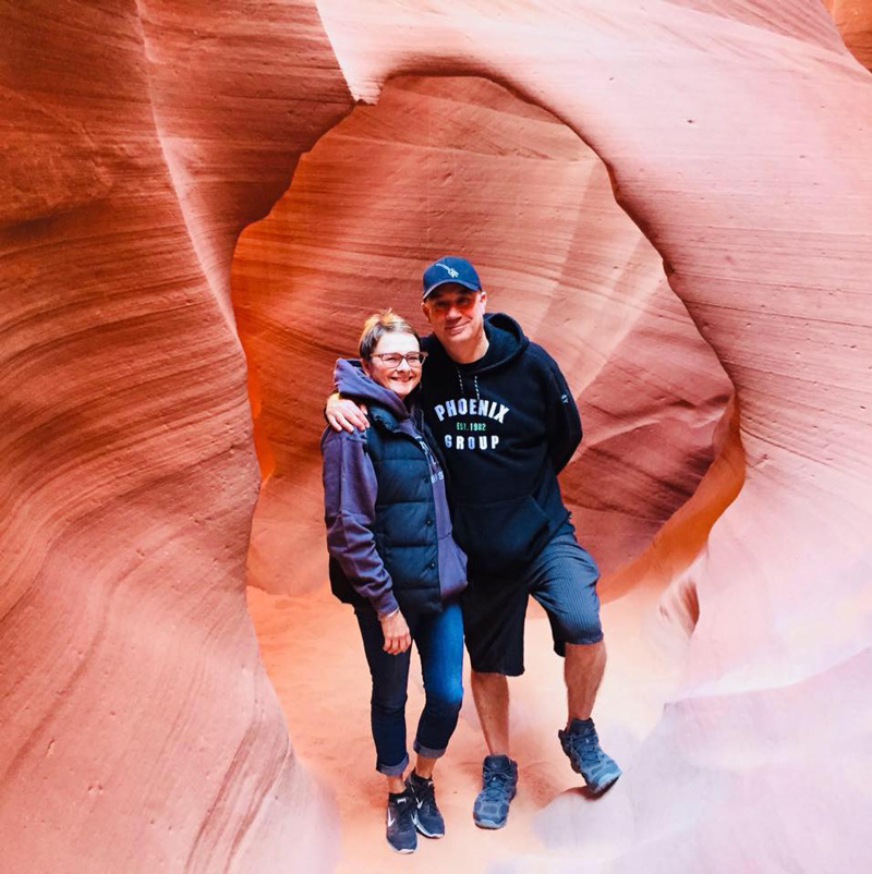 Pam Klein With Husband Stephen Holding Each Other For Photo inArizona Rock National Park