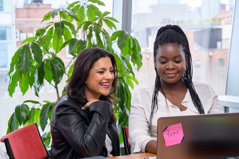 Reshma Saujani Sitting With Black Student Of Girls Who Code Looking And Smiling At Computer Screen
