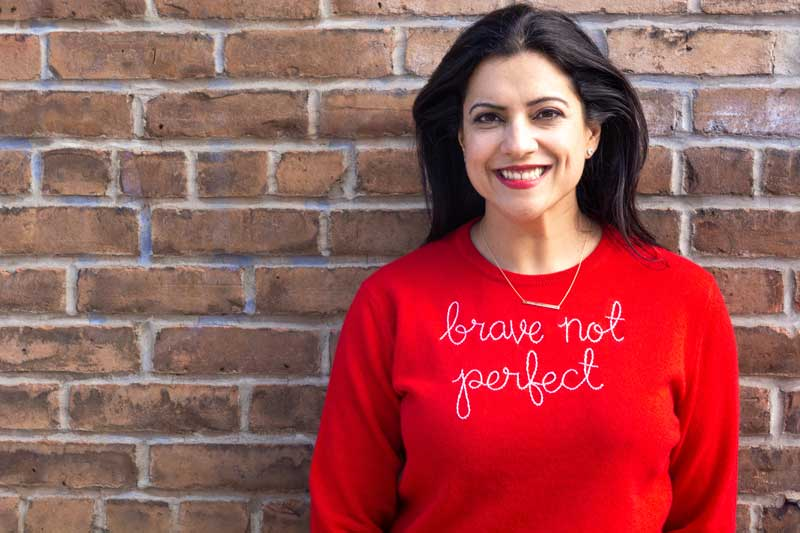 Reshma Saujani Against Brick Wall Wearing Red Shirt With Brave Not Perfect Written On It