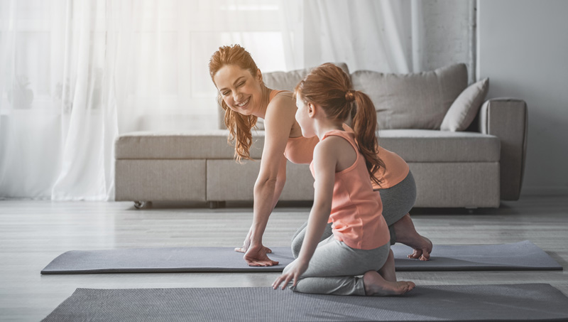 Mother Smiling To Daughter While Doing Yoga Together In Living Room