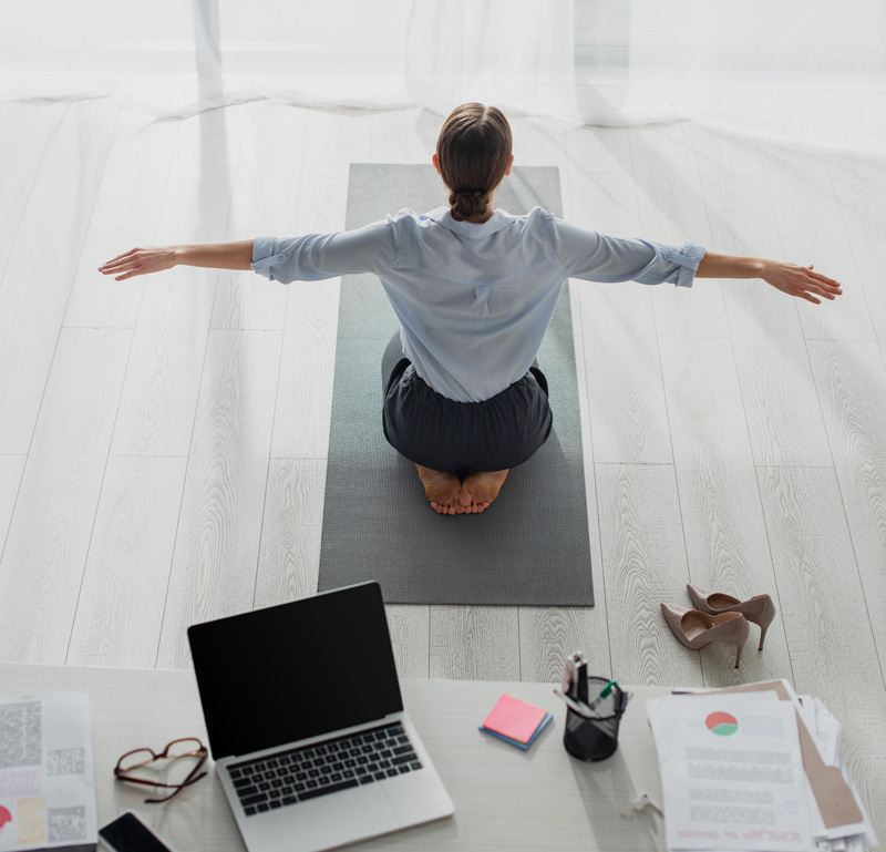 Woman On Knees Doing Yoga In Office Setting